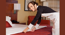 Hotel Maid making bed